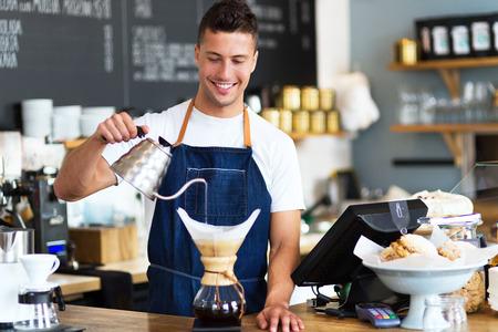 hombre tomando cafe: Barista vertiendo agua en un filtro de caf�