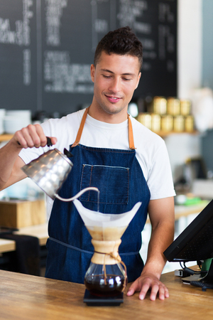 coffee filter: Barista pouring water into a coffee filter