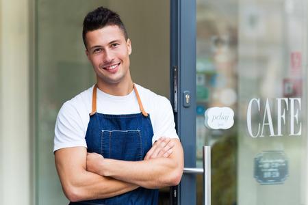 Trotse jonge cafe eigenaar in deuropening