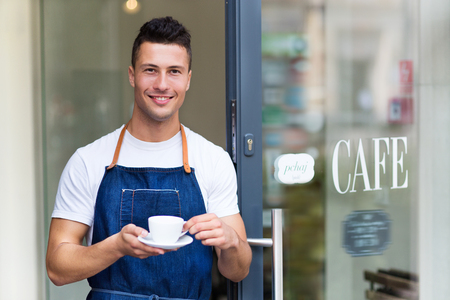 service entrance: Proud young cafe owner in doorway