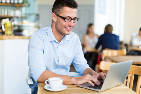 coffee table: Young man using a laptop at a cafe Stock Photo