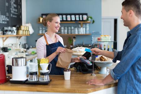pagando: Barista sirve al cliente en una cafetería
