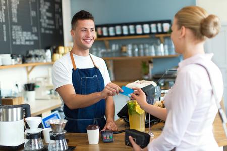 Vrouw betalen voor koffie Stockfoto - 46982673