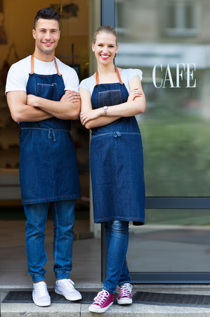 Young cafe owners in doorway 스톡 콘텐츠