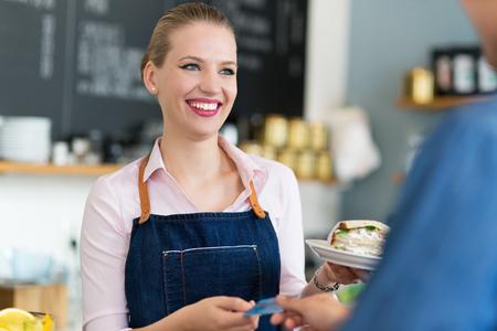 pagando: Camarera que sirve al cliente en el café