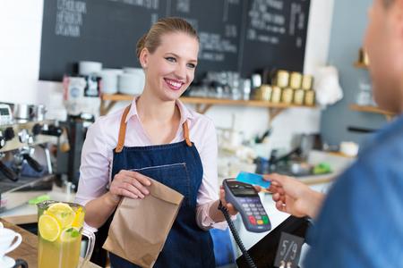 tarjeta de credito: Camarera que sirve al cliente en el café