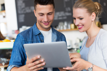 food industry: Young cafe owners looking at a laptop