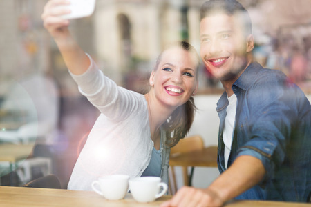 woman window: Couple taking a selfie with smartphone