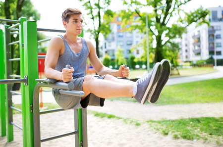 Young man exercising at outdoor gym photo