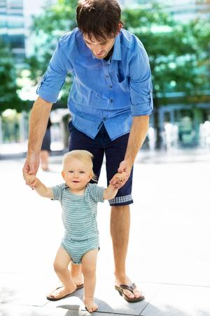 caras felices: Beb� que toma las primeras medidas con padres ayudan Foto de archivo