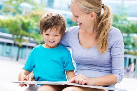 kids outside: Mother and son reading a book Stock Photo