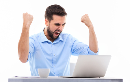 clenching fists: Man in front of laptop with arms raised