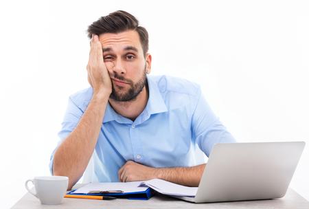 Znudzony młody człowiek przy biurku