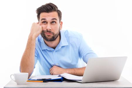 Hombre joven aburrido en el escritorio Foto de archivo - 50031660