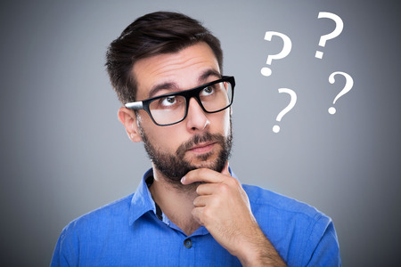 questions: Man thinking with question marks Stock Photo