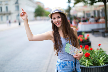 Tourist waving for a taxi on city street Stock Photo