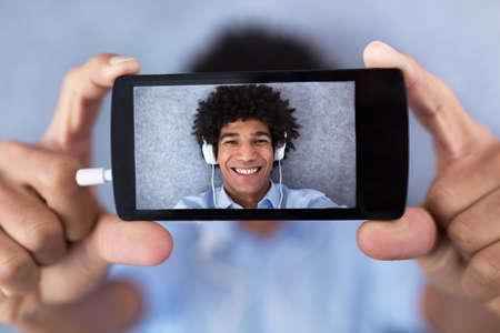 cell phone: African American man taking selfie