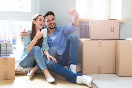 Couple on floor next to moving boxes Standard-Bild