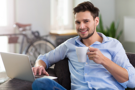 couch: Man sitting on couch with laptop