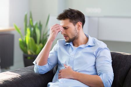 abdomen plano: Hombre en el sofá que tiene dolor de cabeza