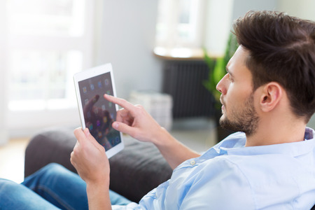 couch: Man sitting on couch with digital tablet