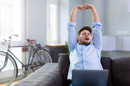 couch: Man stretching on couch