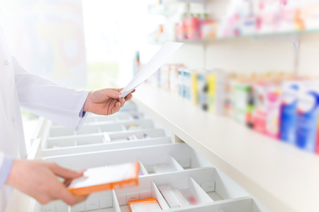 Pharmacist filling prescription in pharmacy Banco de Imagens