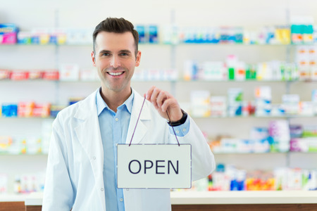 open sign: Pharmacist Holding An Open Sign Stock Photo