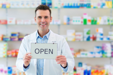 selling service smile: Pharmacist Holding An Open Sign Stock Photo