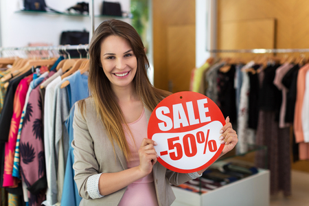 sale sign: Woman with sale sign in clothes shop Stock Photo