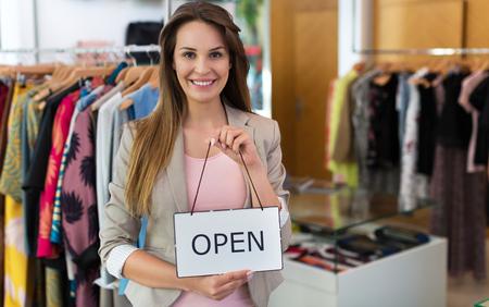 Mujer que sostiene la muestra abierta en la tienda de ropa Foto de archivo