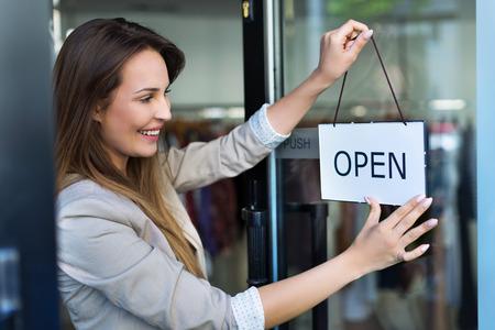 Vrouw opknoping open teken op de deur