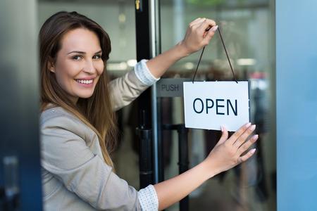 Kobieta wiszące otwarte znak na drzwiach