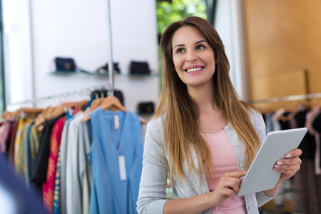 Boutique eigenaar met behulp van een digitale tablet Stockfoto - 57749967