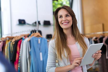 tienda de ropa: propietario de la tienda utilizando una tableta digital