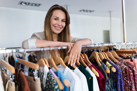 customer tailor: Sales assistant leaning on a clothing rail Stock Photo