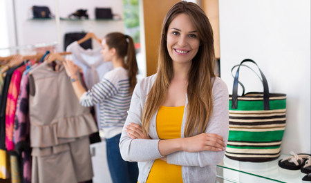 clothes rail: Woman standing in a clothing store