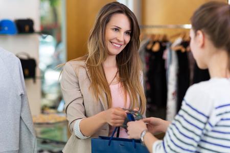 tienda de ropa: Mujer que paga con tarjeta de crédito en una tienda de ropa Foto de archivo