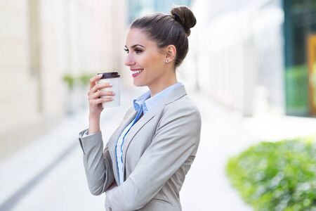 disposable cup: Businesswoman holding disposable cup outdoors