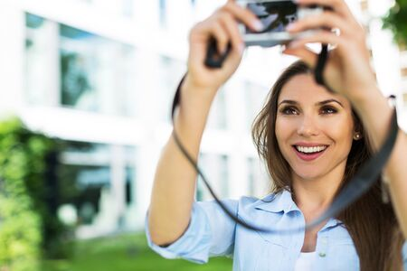 taking photo: Woman taking photo outside Stock Photo
