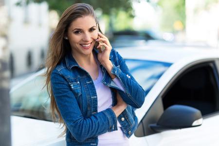 annuities: Woman using mobile phone near car Stock Photo