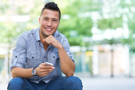 one man: Young man with smartphone outdoors