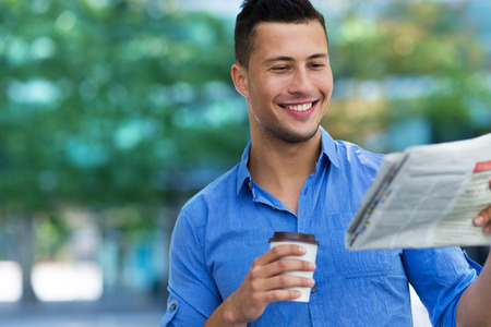 to go cup: Man holding newspaper and coffee