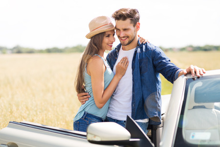 Young couple standing near convertible Stock Photo