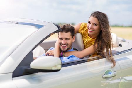 getting away from it all: Couple enjoying a drive in a convertible