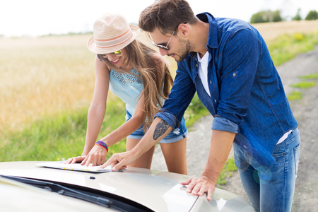 person reading: Couple reading a map while standing near convertible Stock Photo