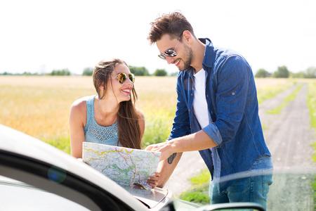 poblíž: Pár čtení mapy, když stál u kabrioletu Reklamní fotografie