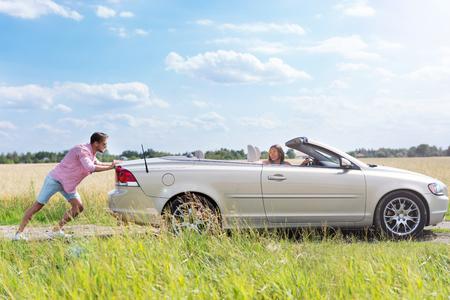 empujando: Hombre que empuja un coche averiado
