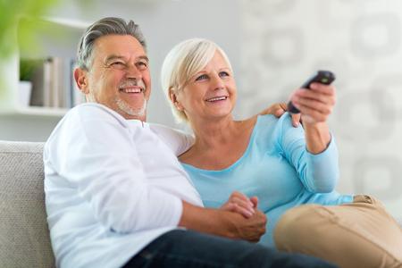personas viendo television: Pares mayores con el control remoto Foto de archivo