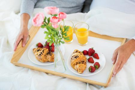 Pares mayores que gozan del desayuno en la cama